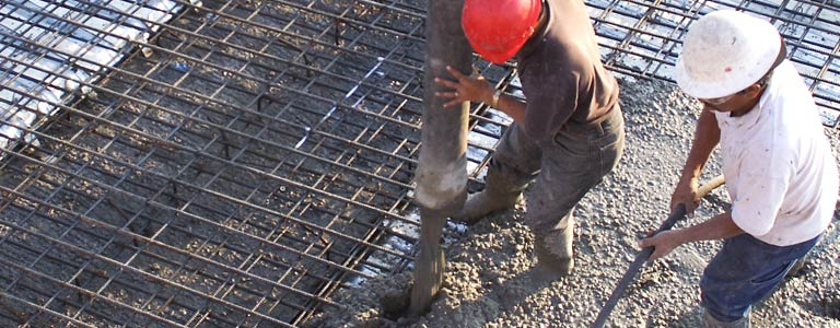 Workers pouring cement on Matching Rebar Deck